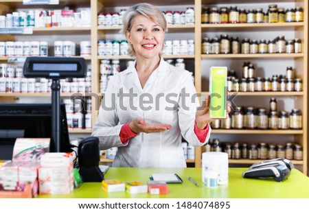 Cheerful positive  mature female seller suggesting useful skin care products in specialized shop