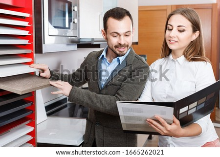 Cheerful positive pleasant  polite saleswoman helping man to choose materials for kitchen furniture in shop