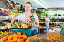Cheerful positive smiling woman standing with full shopping cart during shopping in fruit store
