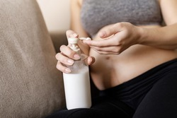 Cheerful pregnant woman taking care of her belly skin creaming it