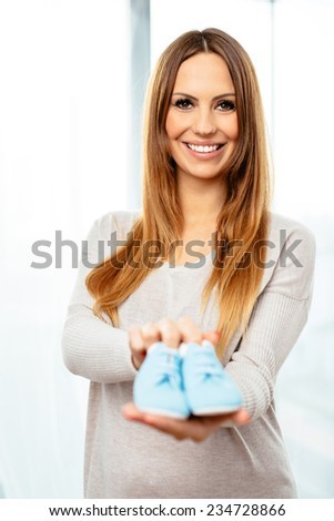 Cheerful pregnant woman with a pair of blue baby boots #234728866