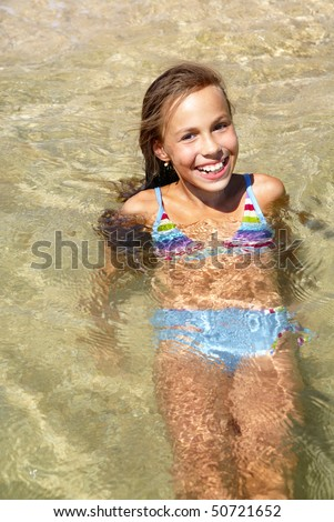 Cheerful preteen girl swimming in sea - stock photo