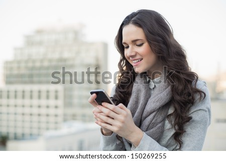 Cheerful pretty brunette in winter clothes sending a text on her smartphone outside on a cloudy day