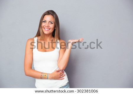 Cheerful pretty girl holding copyspace on the palm over gray background