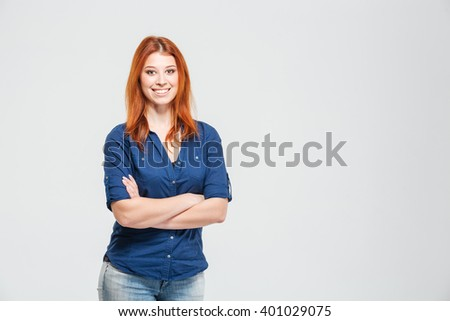 Cheerful pretty redhead young woman standing with hands folded over white background #401029075