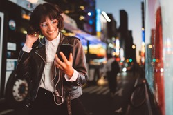 Cheerful pretty young woman in cool eyeglasses and trendy wear walking on metropolis street with night lights enjoying online playlist songs in earphones and reading sms with good news on smartphone