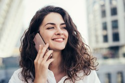Cheerful pretty young woman talking on phone and look straight ahead. Holding smartphone close to ear. Standing alone outside. White buildings behind. Daylight