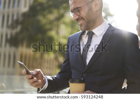 Cheerful professional experienced male editor of financial magazine monitoring work of journalist on internet reading latest publication on website satisfied by creative articles during break outdoors #593124248