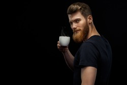 Cheerful professional handsome project manager in black t-shirt holding coffee cup drinking morning espresso coffee standing on black background Bearded man is tasting coffee
