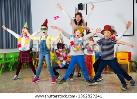 Cheerful pupils and female teacher with funny hats and festive accessories posing together in schoolroom #1362829241