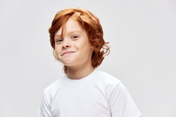 Cheerful red-haired child in a white T-shirt smile studio close-up