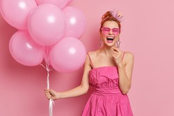 Cheerful redhead woman dressed in pink dress and sunglasses has fun on graduation party poses with bunch of inflated balloons laughs out gladully poses indoor. Female spends free time on prom night