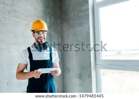 cheerful repairman in helmet and goggles holding digital tablet  #1479481445