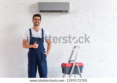 cheerful repairman showing thumb up while standing under air conditioner near stepladder and toolbox #1399172705