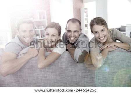 Cheerful roommates sitting in sofa at home #244614256