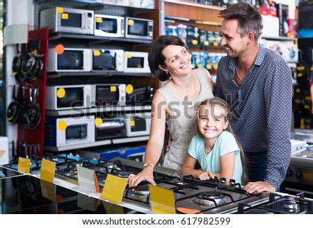 cheerful russian  family with girl shopping gas-cooker in shop of household appliances  #617982599