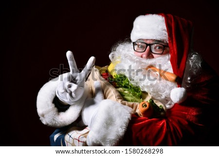 Cheerful Santa Claus is holding a big bag full of fruits and vegetables. Shows shows peace sign with fingers, victory of the right hand. Enjoy a healthy Christmas dinner. Healthy Recipes.  diet.