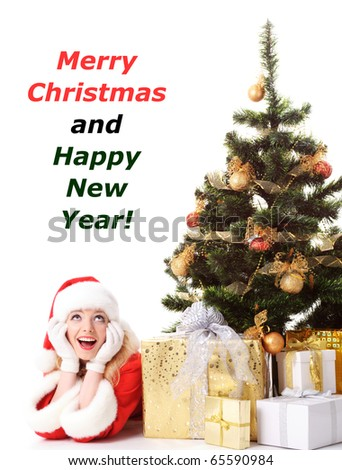 cheerful santa girl lie near the gift and New-year's tree. Copy text. Christmas greetings card