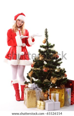 cheerful santa girl stand near the gift and New-year's tree. Copy text. Christmas greetings card