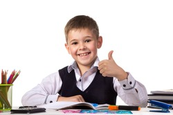 Cheerful satisfied pupil sitting at the desk with thumb up surrounded with stationery