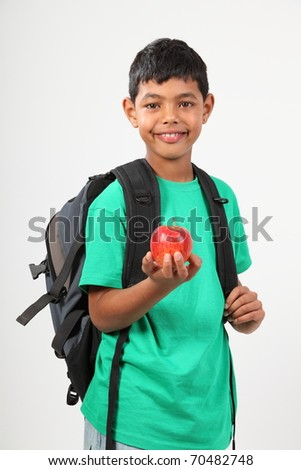 Cheerful school boy smiling holding red apple