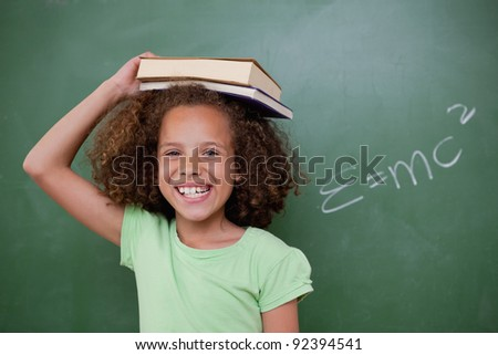 Cheerful schoolgirl holding her book on her head in front of a blackboard - stock photo