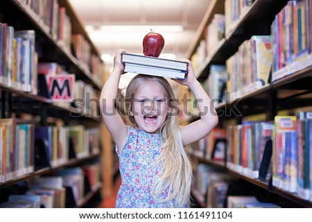 Cheerful schoolgirl holding the books with apple above her head. Education or back to school or wisdom concept.  #1161491104