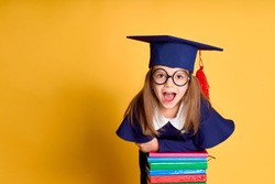 Cheerful schoolgirl in graduation outfit smiling while leaning on pile of colourful books over yellow background