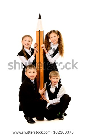Cheerful schoolgirls and boys stand together and hold a huge pencil Educational concept Isolated over white