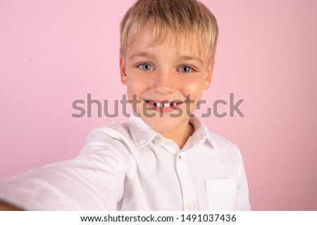 Cheerful selfie. Cheerful young boy in shirt holding mobile phone and making photo of himself while standing against pink background. #1491037436