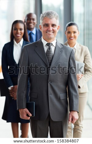 cheerful senior business leader standing in front of his team in office