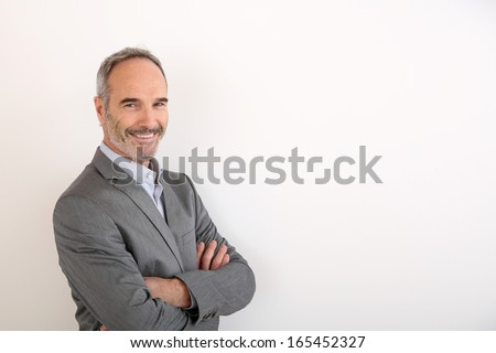 Cheerful senior businessman standing on white background