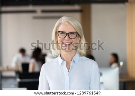 Cheerful senior businesswoman in glasses looking at camera, happy older team leader ceo manager, female aged teacher professor or mature executive woman mentor smiling in office head shot portrait