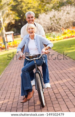 cheerful senior couple cycling in a park