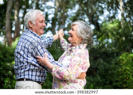Cheerful senior couple dancing against trees in back yard