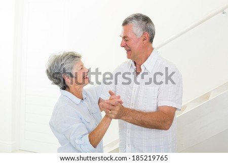 Cheerful senior couple dancing together at home in living room
