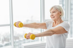 Cheerful senior lady exercising with weights