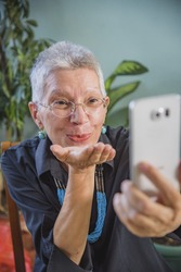 Cheerful senior lady sending kisses to her family and relatives over her cellphone, using skype or viber