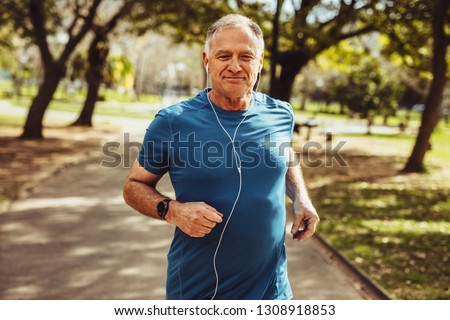 Cheerful senior man jogging in park listening to music on earphones. Senior fitness person running in park for good health.