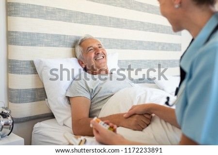 Cheerful senior man lying on bed receiving health care at home. Nurse advising old man on medication at home. Caregiver nurse helping elderly man taking medicine on the bed