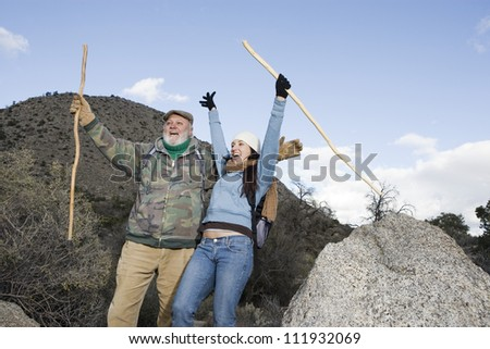 Cheerful senior man with daughter on hiking trip