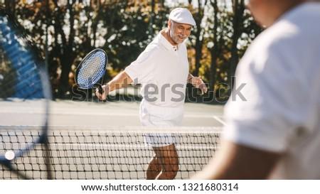 Cheerful senior men enjoying a game of tennis outdoors. Smiling senior man in tennis wear playing tennis with friend.