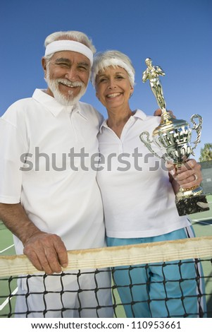Cheerful senior tennis players holding trophy