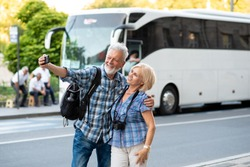 Cheerful senior tourists taking selfie