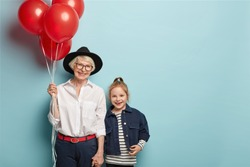 Cheerful senior woman and little granddaughter hold hands, have positive attitude, glad facial expressions, wears stylish outfit, come on festive event devoted to Children Day. Two generations