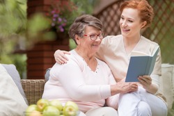 Cheerful senior woman with her tender caretaker reading a book together while relaxing outside. Close relationship.