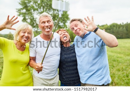 Cheerful seniors make faces and silly around for the selfie photo