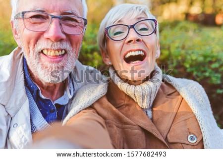 Cheerful seniors using modern technology. Taking selfie photos.