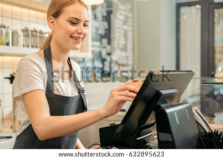 Cheerful shop assistant using digital device for payment Сток-фото ©