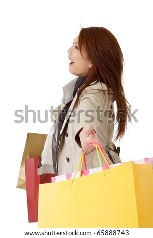 Cheerful shopping woman holding bags and smiling over white.